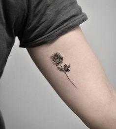 Single needle rose tattoo on the left inner arm.
