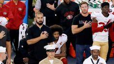 San Francisco 49ers quarterback Colin Kaepernick, middle, kneels during the…