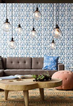 Sala de estar cheia de detalhes e muita personalidade! Papel de parede estampado azul, luminária de pendentes e mesa de centro baixa rústica.