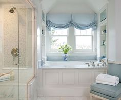 Add a luxurious touch with a soft Roman shade. The blue hues of this window treatment work perfectly in the white bathroom. Other blue accents create a soothing, timeless look.