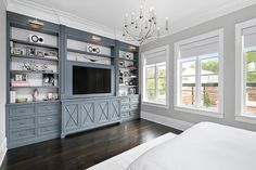 A bed dressed in white hotel bedding sits on a white rug facing gray built-in shelves painted in Benjamin Moore Gunmetal with white backs and fitted with a flat panel television mounted above x-front cabinets flanked by drawers accented with nickel hardware lit by polished picture lights.