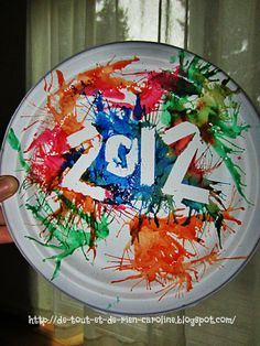 Create a commemorative plate of 2012 with fireworks using tape resist technique and straw painting.