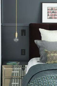 <p>Dans la chambre, les architectes d'intérieur ont opté pour du gris apaisant, décliné en plusieurs teintes. La tête de lit en velours concourt à donner...