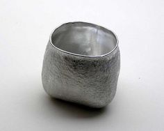 """Sake cup"" by Seikado.  It is made by hitting a relatively thin sheet of pewter using hammers and wooden mallets, and choosing to stretch or raise the metal depending on the section. The rough surface is a texture called ""Ishime""(meaning stone pattern), which is created in a traditional method using a hammer."