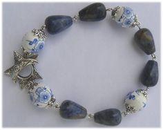 R10 - Pulseira com contas brancas com desenho de flor em azul e peças em forma de cone em azul escuro.   Fecho metálico com uma estrela e uma lua.