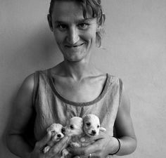 Roger Ballen, Wife of abbatoir worker holding three puppies, 1994
