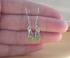 Stunning pair of sterling silver, flame design earrings sret with genuine peridot gemstones. Each earring measures 20mm length x 7mm width.