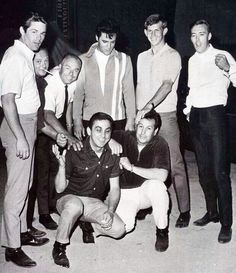 This is the 1967 lineup of the Memphis Mafia. Standing from L - R- Jerry Schilling, Marty Lacker, the two men on either side of Elvis are unidentified, Richard Davis. Kneeling - George Klein on the left - Joe Esposito.