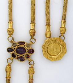 Gold body-chain, consisting of four chains joined at two plaques.  The chains passed over the shoulders and under the arms of the wearer, with a decorative focus where they join on the chest and the back.. The two plaques where the chains join comprise a gold coin of Emperor Gratian (reigned AD 367-383) in a decorative mount, and an oval setting for nine gems, a central amethyst, four garnets, 4th century A.D. Roman