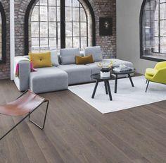 Salón urbano y moderno decorado con muebles coloridos, grandes ventanales y paredes de ladrillo. El #suelo de #parquet Roble Grafito le da un toque elegante al entorno.   #homedesigne #interiorismo #diseño #home #hogar