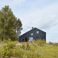 An asymmetrical gabled house by Grzegorz Layer sits near the pine forested shores of Lake Gowidliński in northern Poland.