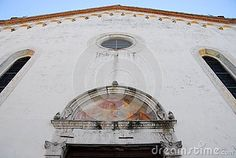Photo taken in Oderzo in the province of Treviso in the Veneto region (Italy). The picture shows the upper part of the white facade, taken from the bottom and from near the dome. in particular they see the four elements, the rose window, the two side windows and the semicircle above the entrance.