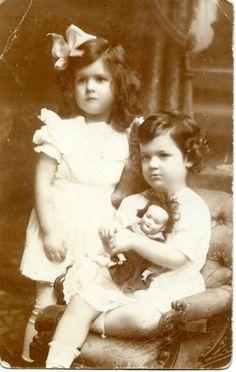 Hermanas posando, una de ellas abrazando su muñeca preferida. Fotografía tomada entre 1910 y finales de 1920.