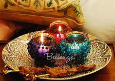 Colored globe tea light lanterns atop mosaic Moroccan plate