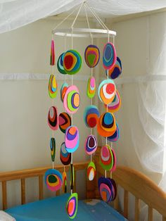 SO easy - and cheap! make the circles so the thread goes through the middle. can be seen when the child is laying down.