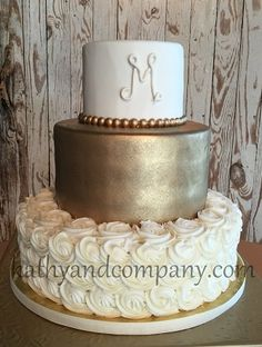 Gold tier wedding cake with rosettes.
