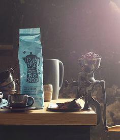 Una confezione di caffè espresso, in grani, mostrato insieme a una vecchia macina-caffé
