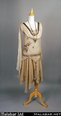 1920s beige rayon day dress with with sequin design detail, attached scarf, and long gold necklace.