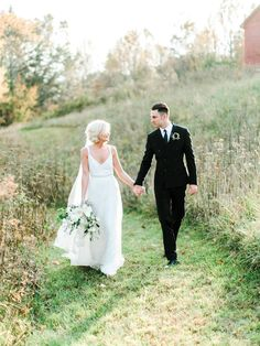 Bride and groom walking hand in hand. Dress by BHLDN, bouquet by Petal Flower Company. Image by Rachel May Photography.