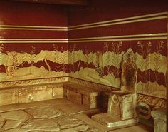 """Throne room of the palace of Knossos, Crete. The """"Throne of Minos"""" is of stone and embedded in the wall of a dark chamber (15th BCE). The griffin frescoes on the wall are restored from surviving fragments."""