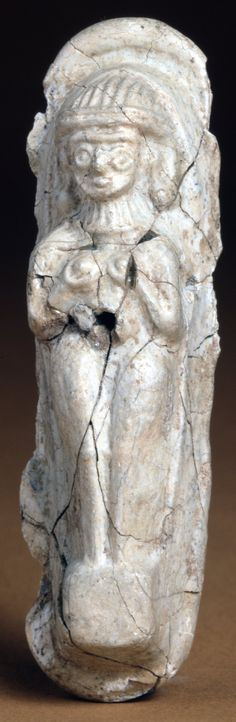 ca. 1500-1400 BCE, Late Bronze Age 1. A major female deity, presumed to be Astarte, figures of this type have been found from The Med to the Near East.  Mould-cast glass plaque pierced for suspension; naked standing on a square plinth; holding her breasts. From Tel Atchana; in Alalakh ancient Turkey founded by western semitic tribes the Amorites from Syria during the Middle Bronze Age who adopted Sumerian culture.