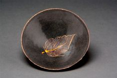Jizhou Kiln leaf temmokus...   There is still some controversy as to how these were actually made but NH Koh on his website suggests that the amber colour is indicative of a layer of glaze covering the leaf before firing & hence the slight raising of the leaf image... Asian Art Forums