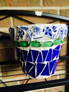 Clay flower pot covered with blue glass, green oblong marbles and broken blue and white dishes.