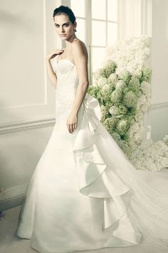 Strapless duchess satin gown features veiled tulle bodice with exquisite geometric seaming and lace applique detail. Truly Zac Posen, David's Bridal