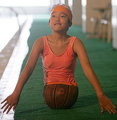 """Basketball prosthetic on Qian Hongyan. Losing her legs in a childhood accident, Qian Hongyan's family could not afford the prosthetic legs for her, so they improvised with a basketball. She used to move around with the basketball using hand props, but now has new """"legs"""". She is hoping to comete in the 2012 Paralympics."""