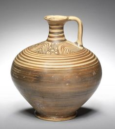A Mycenaean pottery jug  Late Helladic IIIC, circa 1200-1100 B.C. Ovoid in form, on a ring foot, the slender neck with a flaring rim and strap handle, the body with added slip and encircling bands, the shoulder with concentric arches and linked diamonds, 8in (20.3cm) high