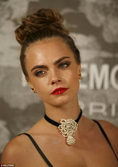 New look: Cara Delevingne showed off her new lip ring when she attended the Chanel exhibition party at London's Saatchi gallery on Monday night