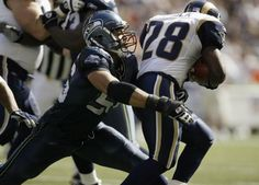 Running back Marshall Faulk of the St Louis Rams is tackled by defensive end Chike Okeafor of the Seattle Seahawks at Seahawks Stadium on September...