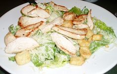 Learn how to make Ceasar salad recipe. This Ceasar salad is made with chicken and grated Parmesan cheese. It has basic ingredients Romaine lettuce, dressing with cheese and chicken.