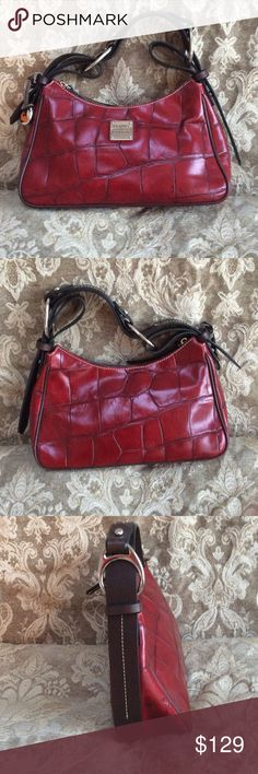 Dooney and Bourke Croco Embossed Leather Hobo This crimson color genuine leather small hobo is beautiful.  It has a zipper closure.  It has an interior zipper compartment and small phone or slip pocket. It has the tradition fob for attaching keys. The single equestrian styled shoulder strap sets this bag apart.  The lining is in good shape and there's some minor wear on the piping shown in the pictures. If you prefer a smaller bag that still makes a statement this is for you. It's great for…