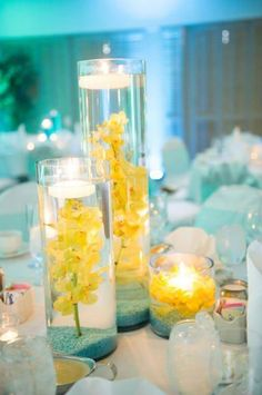 Submerged yellow orchids and floating candle wedding centerpieces. OCLA Events, Southern California.