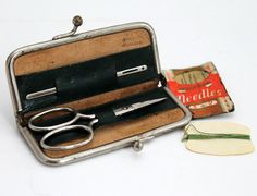 This is a small vintage sewing kit made in Germany by Shear Co. It features a green leather or leatherette case small enough to fit in your purse, car, and great for travel. There is a kiss lock that opens and shuts easily  The kit contains a small pair of scissors, a pack of sewing needles, some thread wrapped around a bit of paper, and a large blunt needle. The scissors and sewing needle pack is marked Germany. Shear Co, Germany is embossed on the inside of the case. There is rust and…