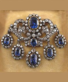A Victorian sapphire and diamond brooch. The principle oval shaped sapphire is set within a surround of cushion shaped diamonds in silver and gold. With a diamond and sapphire set foliate scroll mount and suspending five graduated sapphire and diamond clusters. Fitted case by S.J. Phillips.