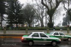Image #8: Taxis speed by Parque Juarez in Xalapa on a misty afternoon. Xalapa is a two hour drive north of Coscomatepec along the eastern flank of the volcano.