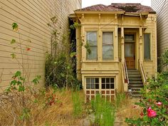 An Abandoned Home in San Francisco sandwiched between two modern apartment buildings on a residential street.
