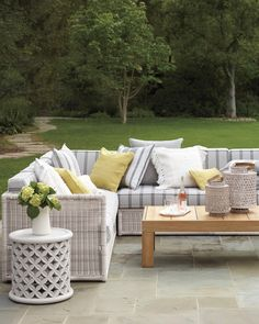 Throw pillow styling adds a pop of color to this gorgeous patio with rattan outdoor furniture, a wooden coffee table, and a basketweave side table. Decor, Furniture, Outdoor Pillows, Porch Furniture, Patio Furniture, Outdoor Side Table, Backyard Decor, Rattan Outdoor Furniture, Teak Patio Furniture