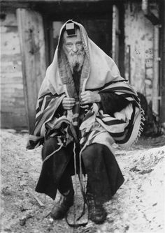 The Kolbuszowa rebbe, Yechiel Teitelbaum, is forced to pose for a photograph in his tallit and tefillin (prayer shawl and phylacteries) in front of his home in the ghetto.    The rabbi was later relocated to the Rzeszow ghetto, where he and his two granddaughters were murdered.