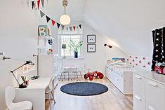 białe łóżko dziecięce z szufladą,okragły granatowy dywan,kolorowe proporczyki i białe biurko w dziecięcym pokoju - Lovingit.pl