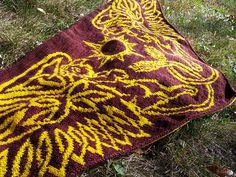 This striking double knit shawl pattern features two gryphons rising around a sun with free-form Celtic knot wings.