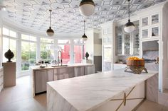 D Home | Regan and Zach Carlile's kitchen — featuring Calacatta Vagli marble, Circa Lighting globe lights, Designers Guild/Osborne & Little wallpaper on the ceiling — is so stunning, it might even make us want to cook.