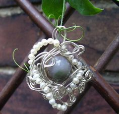 """""""Adventures of the Wandering Planet"""" pendant in silver plate and pearl."""