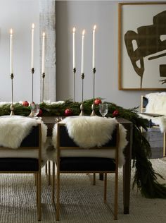 Moody and modern holiday dining room design idea: velvet chairs, sheepskins, with plenty of gold and greenery.
