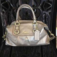 Auth. Coach Ashley Satchel in Gold Leather! This Authentic Coach Ashley Satchel in Gold Leather is simply stunning. The leather feels as good as it looks, and the functional styling makes this bag an all around winner. It is in absolute excellent condition, having only been carried once or twice. This bag can be carried as a satchel, or one can utilize the longer strap that conveniently stows along its base to carry it over the shoulder. The black sateen lining is clean and beautiful. This…