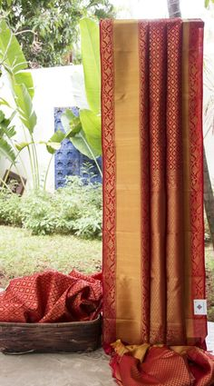 This kanchivaram silk is in crimson red with gold zari brocade work in a geometrical pattern all over the traditional sari. The border and pallu have intricate designs that add to the opulence of t…