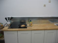 Ikea metal shelves re-purposed into a kitchen back splash.