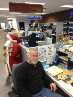 """Michael Connelly sitting at Harry Bosch's desk. Love seeing the sign behind him """"Get off your ass and go knock on doors"""" one of Harry's mottos Authors, Writers, Michael Connelly, Criminal Defense, Crime Fiction, Book Writer, Belly Laughs, Mottos, Knock Knock"""